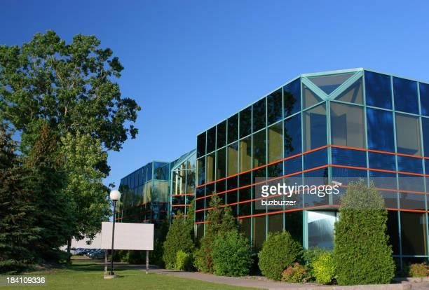 Moderno edificio per uffici con alberi e firmare