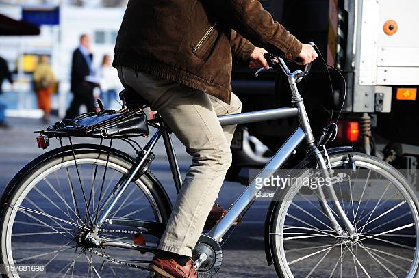 Modern office worker on bicycle in traffic