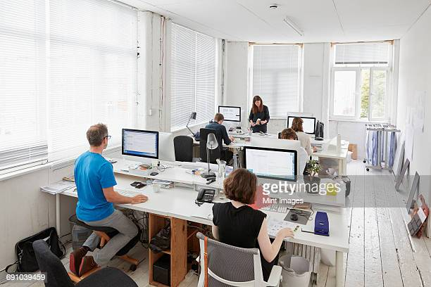 A modern office, workstations for staff. Elevated view of six people seated at desks. A man using an ergonomic kneeler chair.