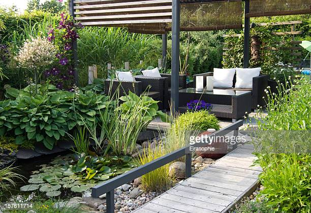 Modern patio garden lounge with a pond and outdoor sofas
