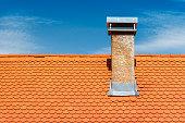 Modern roof with chimney. Orange ceramic tile, shingle. Blue sky on the background.