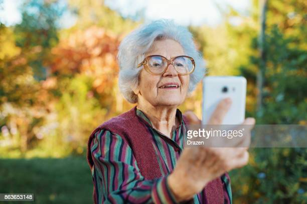 Modern senior woman using smartphone for selfie