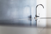 Modern and Shiny Silver Stainless Steel Kitchen Bathroom Tap with Beautiful Reflection and Copy-Space