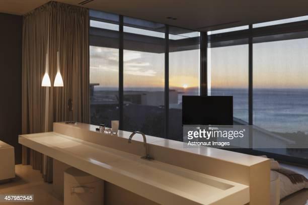 Moderno lavamanos en el dormitorio con vista al mar en la puesta de sol