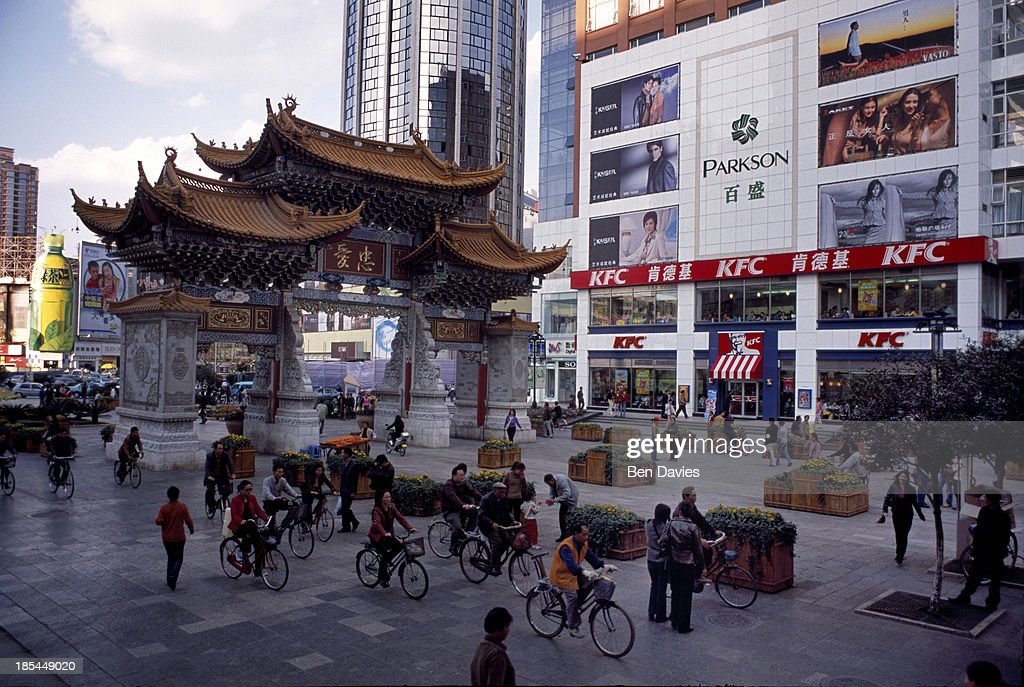 Modern skyscrapers and fast food shops like Kentucky Fried Chicken jostle for space in the city of Kunming in Yunnan Province Southwest China in a...