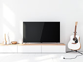Modern Smart Tv Mockup with blank black screen standing on console, modern living room with acoustic guitar. 3d rendering