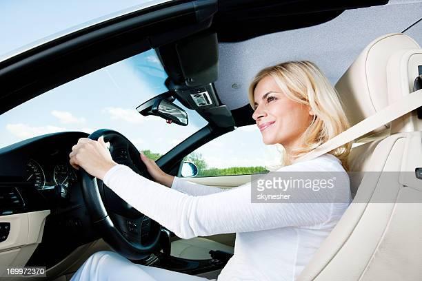 Modern smiling female enjoying in a car ride.