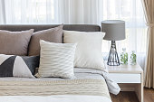 modern style bedroom with pillows on bed and modern grey lamp on side table at home