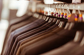 Row of men's suits hanging on the rack in one line