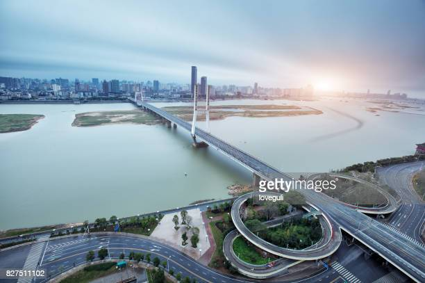 modern suspension bridge over tranquil river and cityscape of modern city
