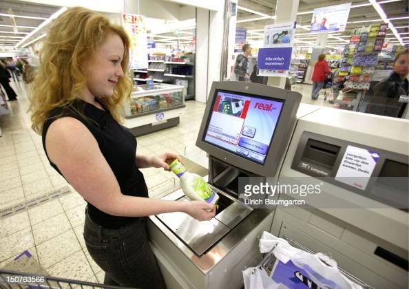 Modern technique makes it happen shopping without cashier Young woman with her shopping goods at a new type of till where the customer scans the...
