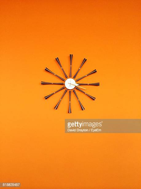 Modern Wall Clock On Orange Wall At Home