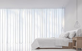 Modern white bedroom minimal style 3D rendering Image.There are decorate room with white translucent curtain and white bed