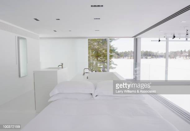 Modern white bedroom with tub in background