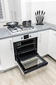 Modern white and black kitchen, open electric oven and gas stove, minimalistic clean design