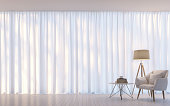 Modern white living room minimal style 3D rendering Image.There are decorate room with white translucent curtain and white armchair