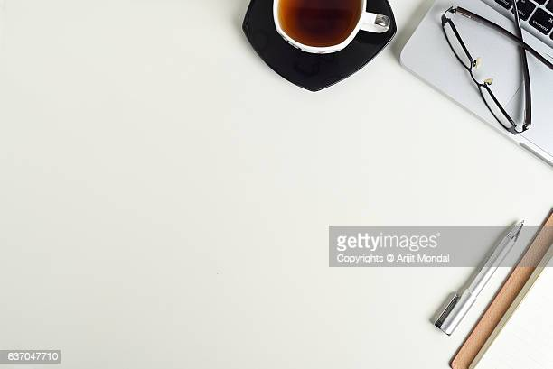 Modern white office desk table with laptop, notepad, pen, green tea and eye glasses