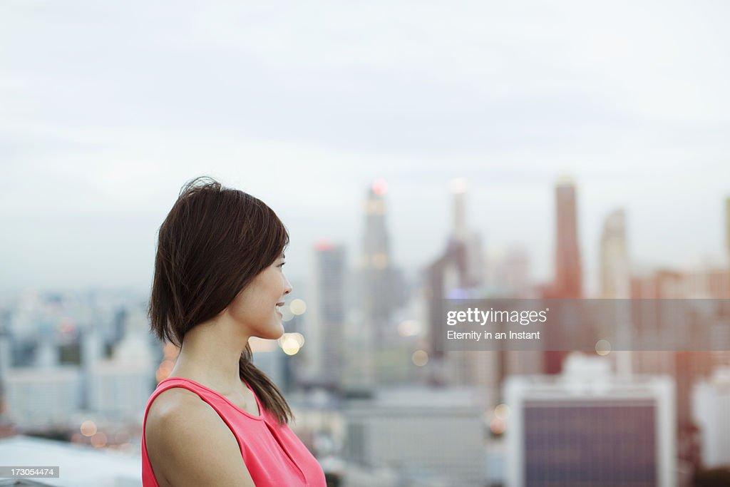 Modern woman looking at city : Stock Photo