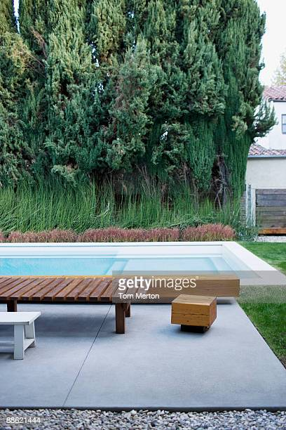 Modern wooden lounge chair next to swimming pool