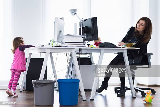 Modern working mother watching little daughter playing in the office