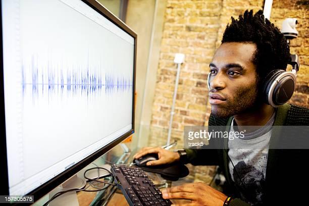 Áudio Engenheiro a trabalhar em Editar uma forma de onda no seu computador