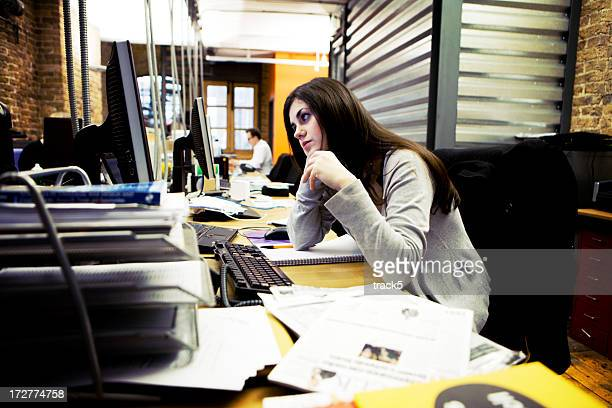 modern workplace: creative professional concentrating at her cluttered desk