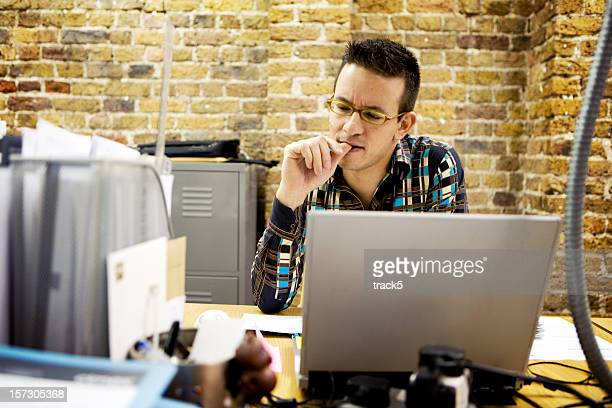 modern workplace: creative professional resolving a problem at his desk