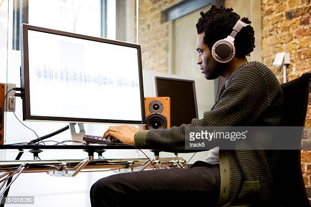 modern workplace: sound editor at his desk editing wave forms