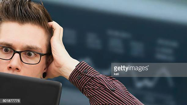Modern young businessman, business-punk, working on a laptop, with a desperate face