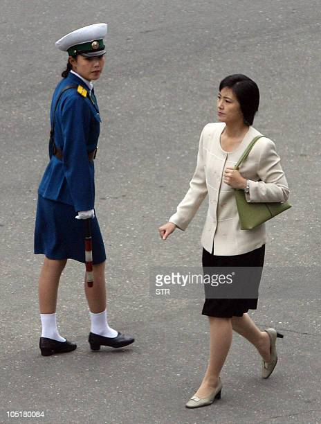 A modernly dressed North Korean woman walks past a traffic officer in uniform in the Changgwang street during the two Korea summit in the capital...