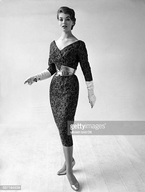 * Modeschöpfer D Nachmittagskleid aus beigeerdfarbenem Wollbrokat mit einem breiten goldfarbenen Ledergürtel Juni 1957