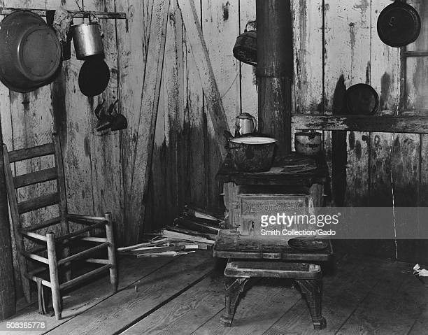 A modest kitchen belonging to a sharecropper with a wellused wooden stove a chair awaiting repairs against the wall and pans and kettles hanging from...