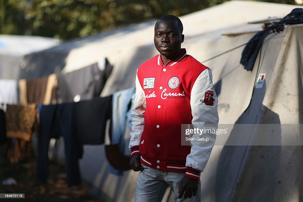Modibo Traore, 28, who is a refugee from Mali, poses for a photograph next to tents at the makeshift camp where he and approximately 100 other refugees are living at Oranienplatz in Kreuzberg district on October 14, 2013 in Berlin, Germany. Traore came to Europe two years ago by boat from Libya to Lampedusa, and eventually made his way to Berlin, where he has now been two months. Berlin authorities have tolerated the camp at Oranienplatz and have promised to move the refugees to proper housing ahead of the coming winter.