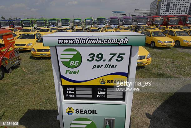 Modified taxis and passenger buses are displayed behind a mock biofuel pump in a Manila parking lot during a launching of public utility vehicles...
