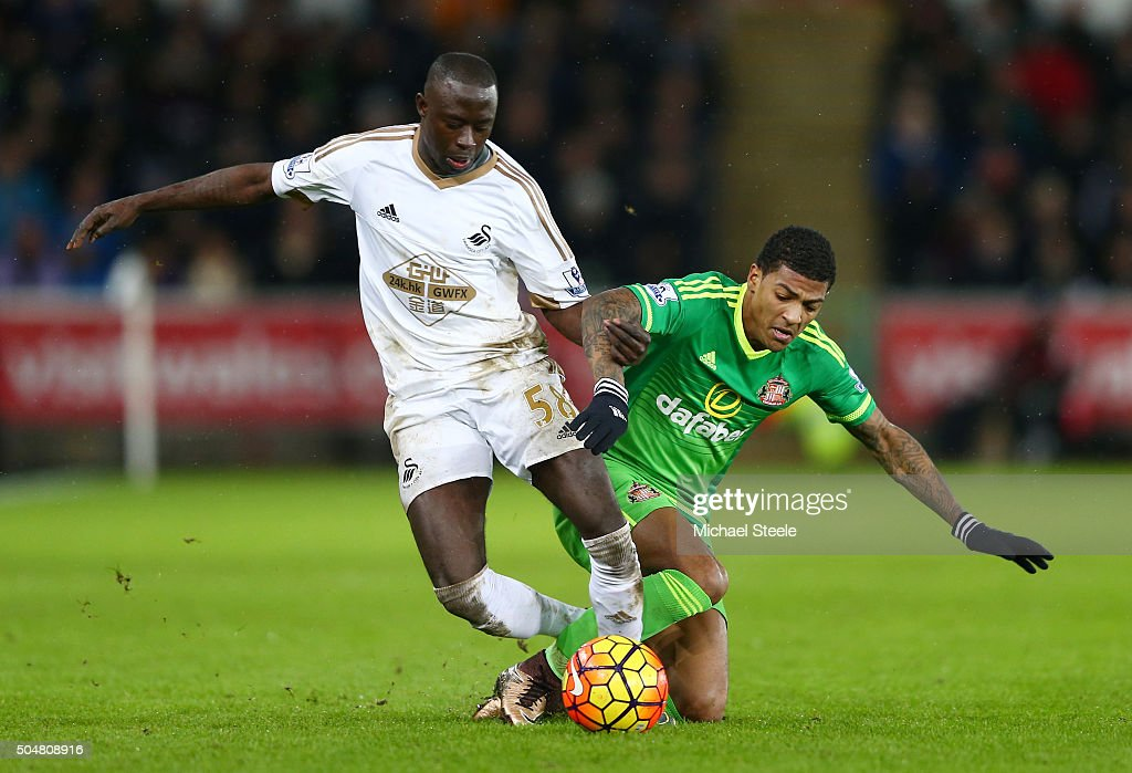 Modou Barrow of Swansea City is challenged by Patrick van Aanholt of Sunderland during the Barclays Premier League match between Swansea City and...