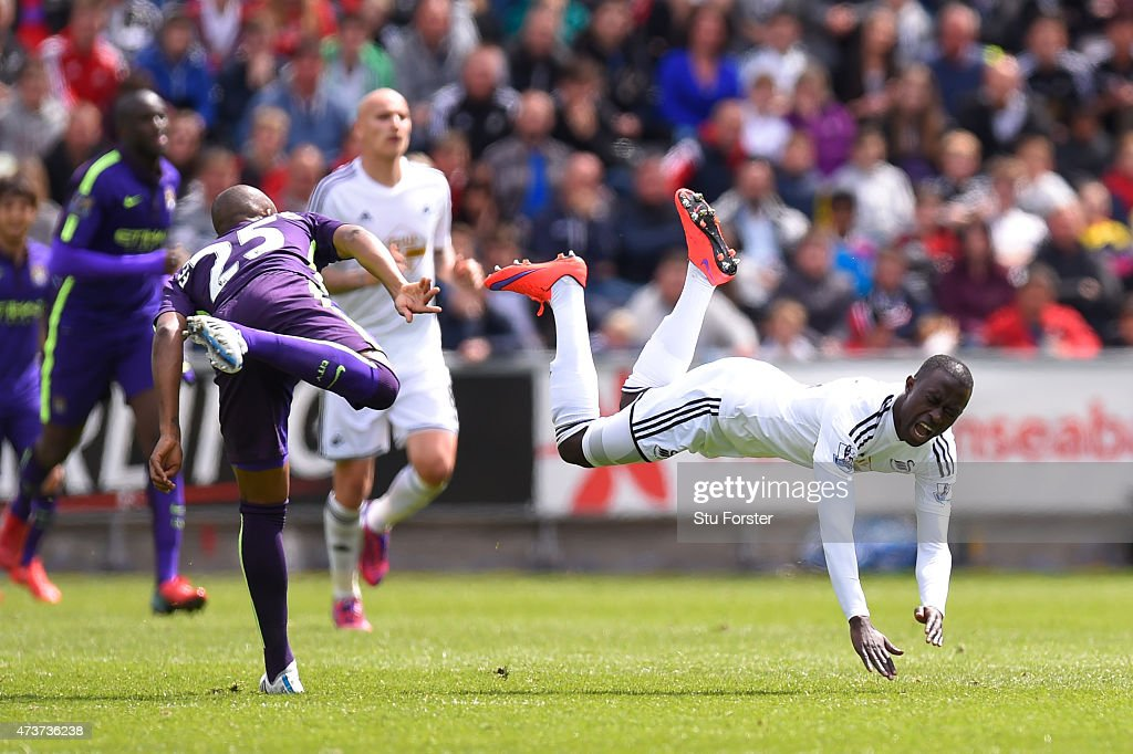 Modou Barrow of Swansea City is fouled by Fernandinho of Manchester City during the Barclays Premier League match between Swansea and Manchester City at the Liberty Stadium on May 17, 2015 in Swansea, Wales.