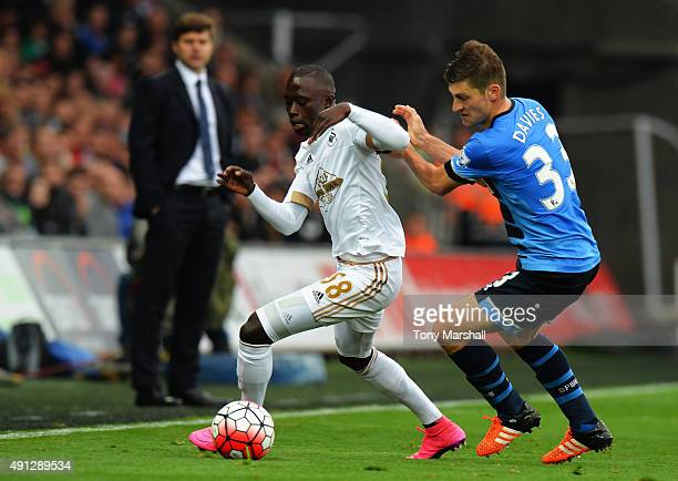 Modou Barrow of Swansea City is marshalled by Ben Davies of Tottenham Hotspur during the Barclays Premier League match between Swansea City and...