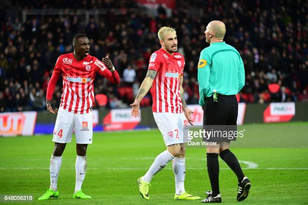 Modou Diagne of Nancy and Erick Cabaco of Nancy protest to referee Antony Gautier about his decision to award a penalty during the French Ligue 1...