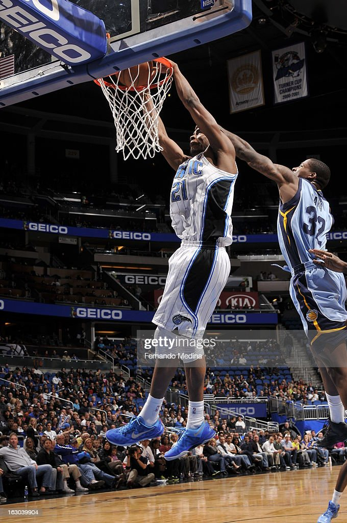 Moe Harkless #21 of the Orlando Magic dunks against Ed Davis #32 of the Memphis Grizzlies on March 3, 2013 at Amway Center in Orlando, Florida.