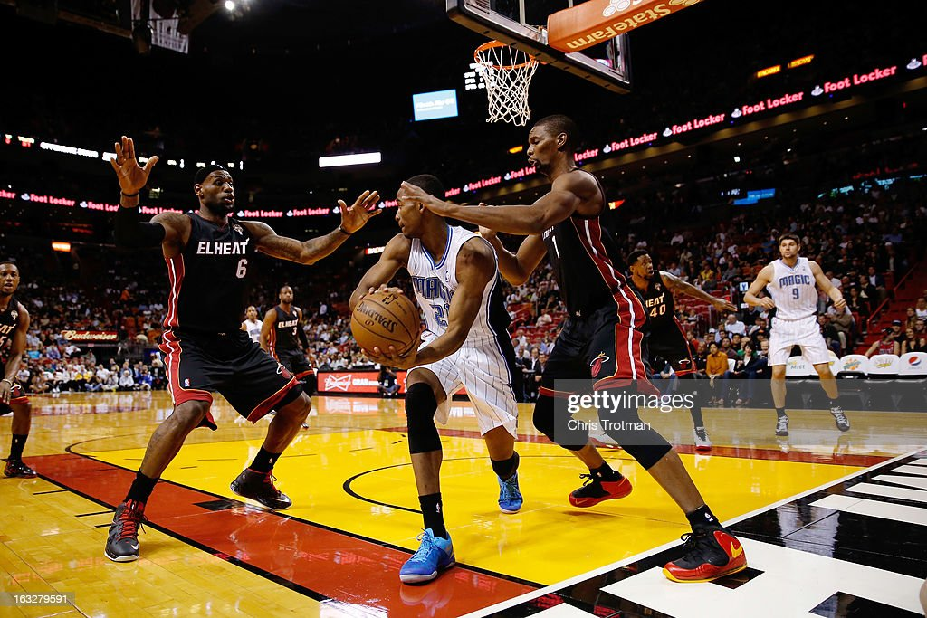 Moe Harkless #21 of the Orlando Magic is guarded by LeBron James #6 and Chris Bosh #1 of the Miami Heat at American Airlines Arena on March 6, 2013 in Miami, Florida.
