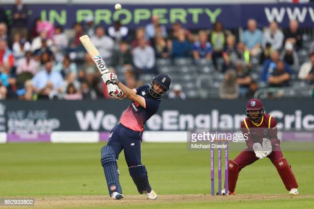 Moeen Ali of England hits out off the bowling of Ashley Nurse as wicketkeeper Shai Hope of West Indies looks on during the third Royal London One Day...