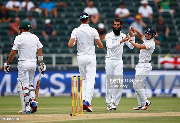 Moeen Ali of England is congratulated after taking the wicket of Dean Elgar of South Africa during day one of the 3rd Test at Wanderers Stadium on...