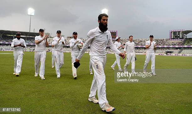 Moeen Ali of England leads his team from the field after taking five wickets during the first day of the 2nd Test match between Bangladesh and...