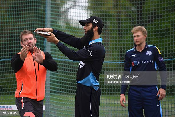 Moeen Ali of Worcestershire is given advice by discus thrower Dan Greaves of Great Britain as Joe Root of Yorkshire looks on during the NatWest T20...