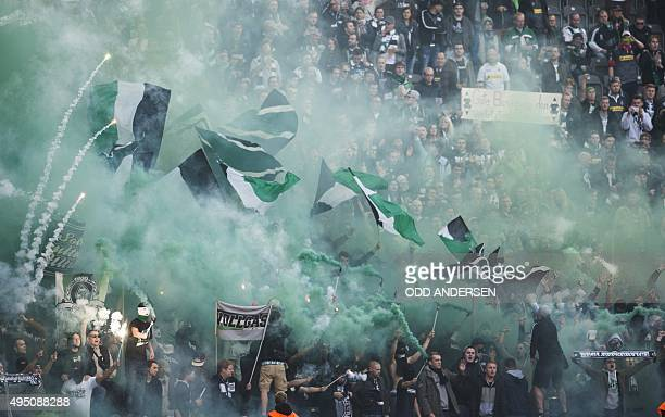 Moenchengladbach fans wave their flags and light pyrotechnics and smoke flares during the German first division Bundesliga football match Hertha BSC...