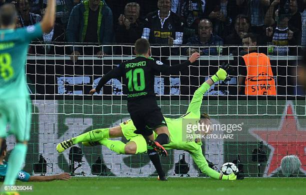 Moenchengladbach's Belgian midfielder Thorgan Hazard scores the opening goal past Barcelona's German goalkeeper MarcAndre Ter Stegen during the UEFA...