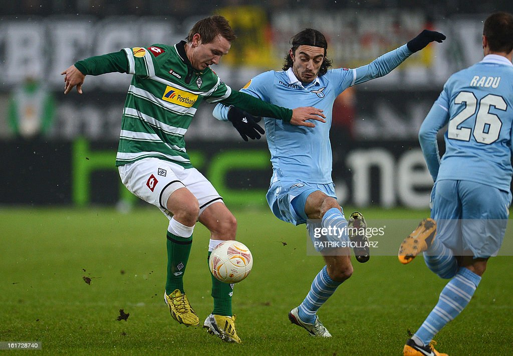 Moenchengladbach's Dutch forward Luuk de Jong (L) and Lazio's defender Giuseppe Biava vie for the ballduring the UEFA Europa League football match VfL Borussia Moenchengladbach vs SS Lazio on February 14, 2013 in Moenchengladbach, western Germany.