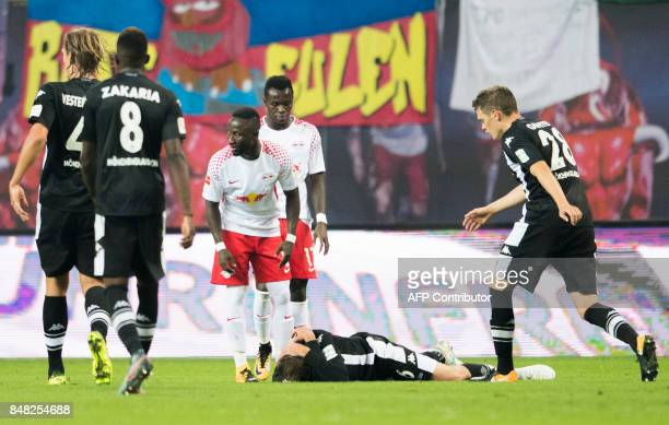 Moenchengladbach´s German midfielder Christoph Kramer lays on the pitch after a heavy foul by Leipzig´s Guinean midfielder Naby Deco Keita during the...