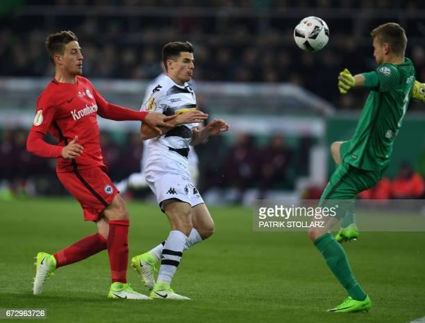 Moenchengladbach's midfielder Jonas Hofmann Frankfurt's Finnish goalkeeper Lukas Hradecky and Frankfurt's Croatian forward Ante Rebic vie for the...