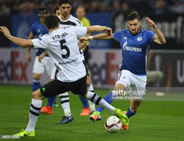 Moenchengladbach's midfielder Tobias Strobl and Schalke's defender Daniel Caliguri vie for the ball during the UEFA Europa League Round of 16 first...